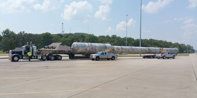 An oversized load parked inside a rest area flanked by two pilot car vehicles.