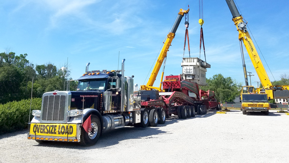 A transformer being offloaded from a 19 axle trailer.