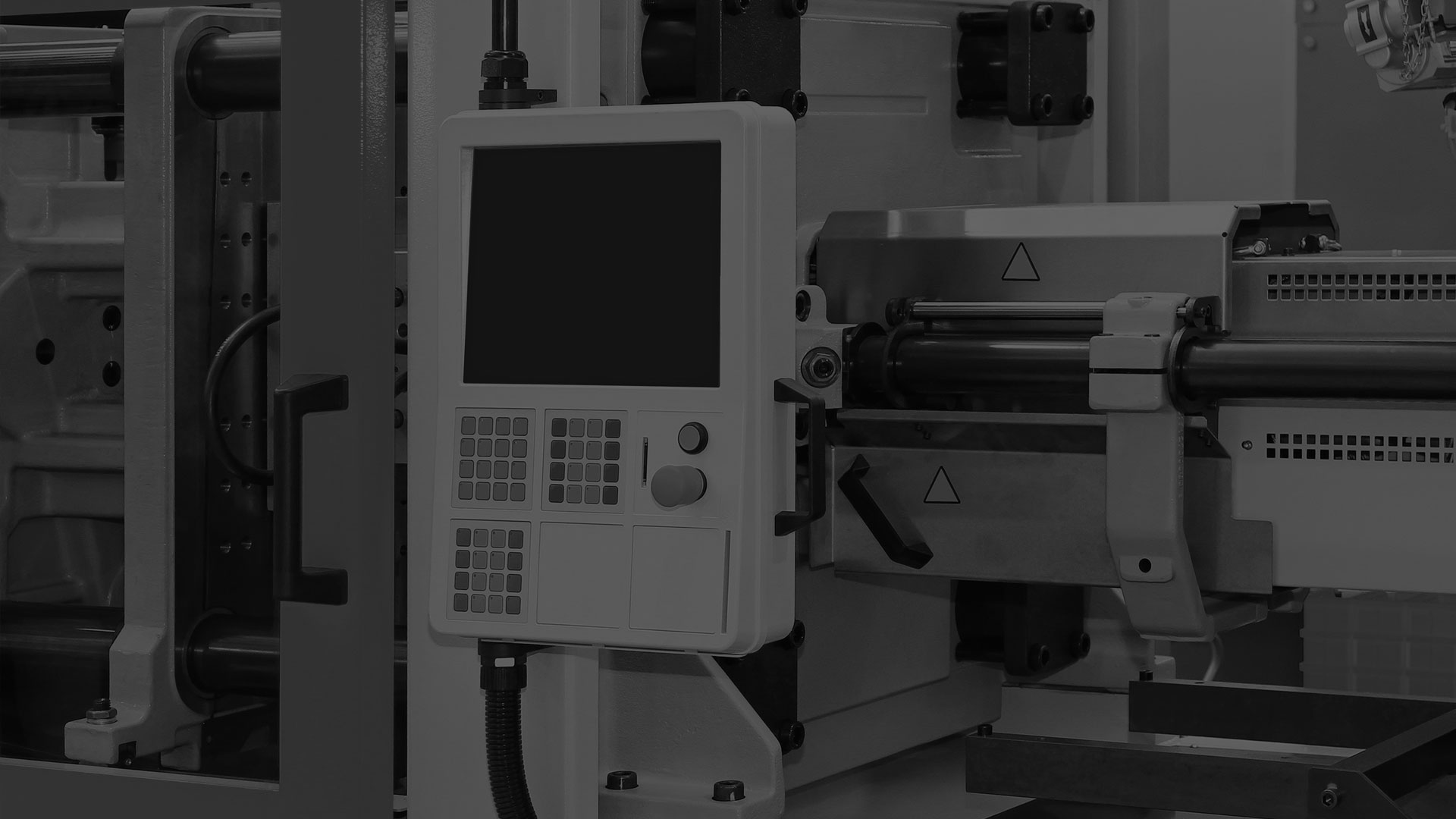 A darkened black and white image of an injection molding machine.