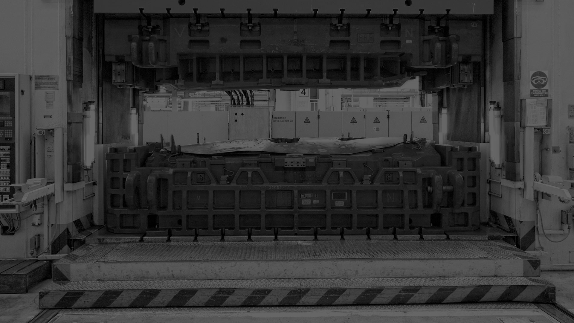 A darkened black and white image of a press system.