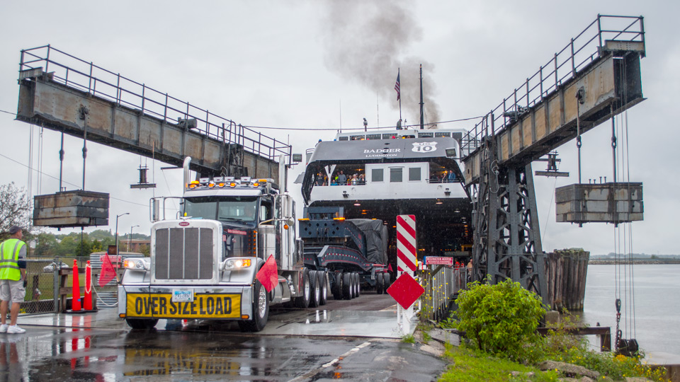 A 20 axle trailer being backed into the underbelly of a ferry.