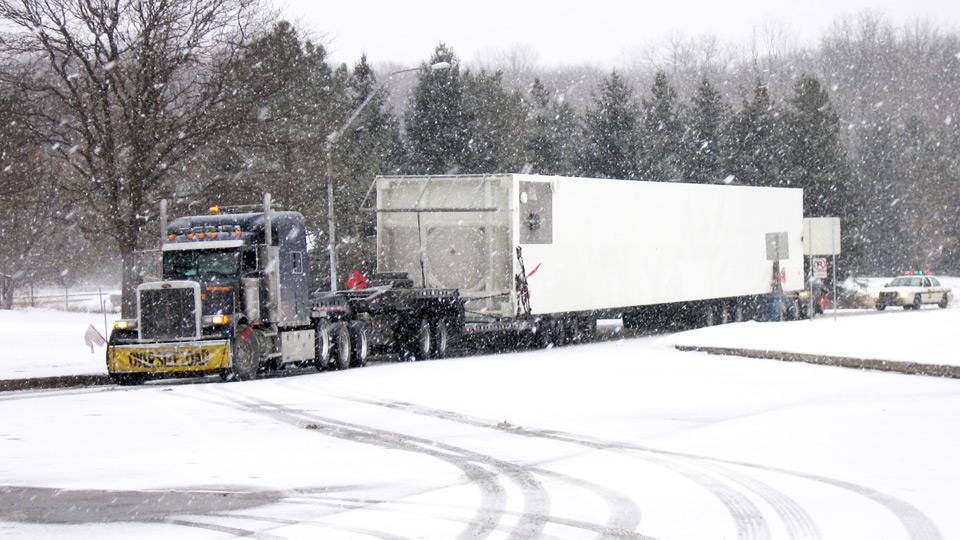 A oversive load makes its way into a rest area through harsh winter conditions.