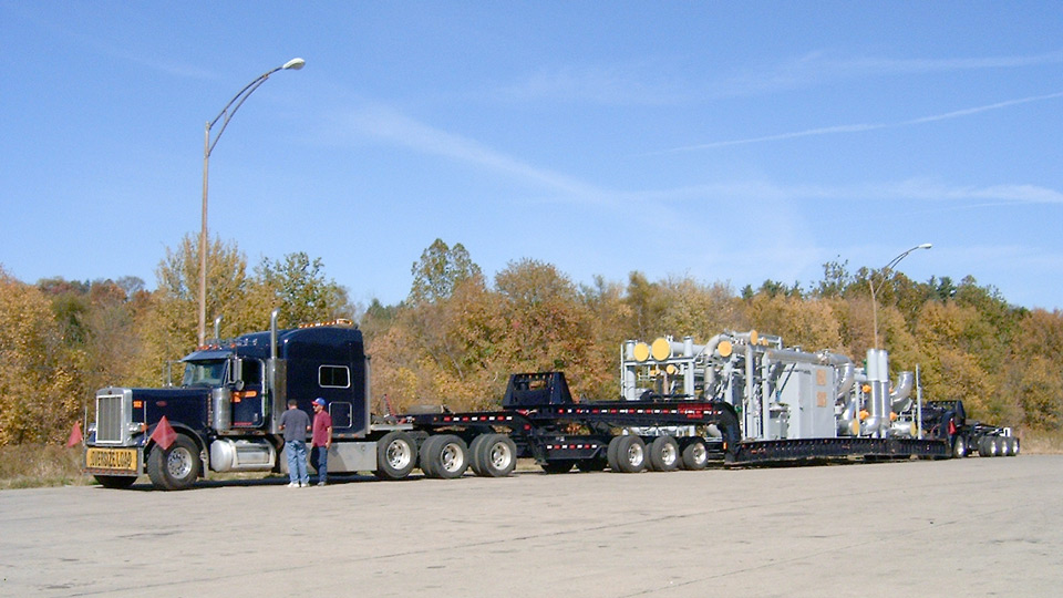 A loaded perimeter 13 axle trailer sitting in a rest area loaded with an oil and gas rig.