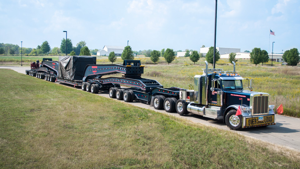 A 20 axle rig loaded with a Press Crown outside a customers facility.