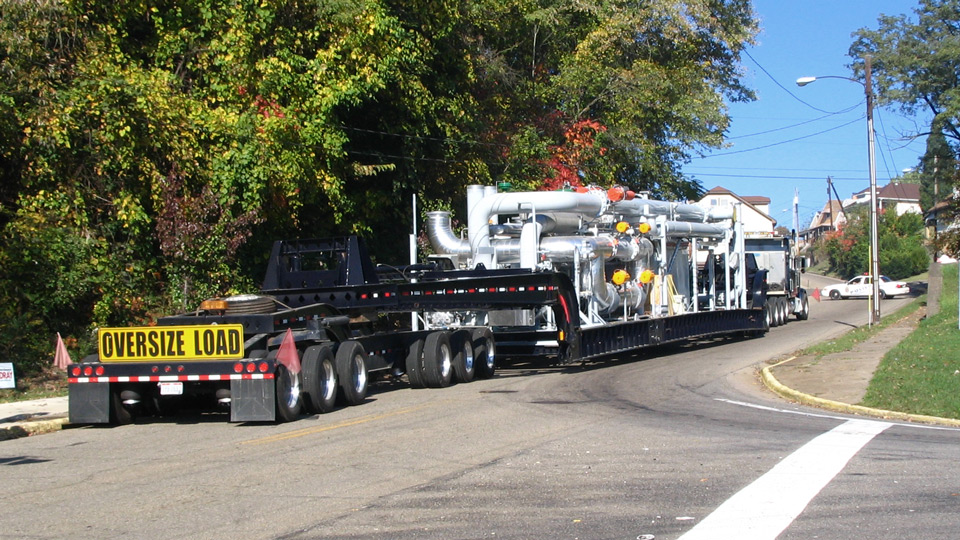 A superload makes its way up a hill on narrow city streets.
