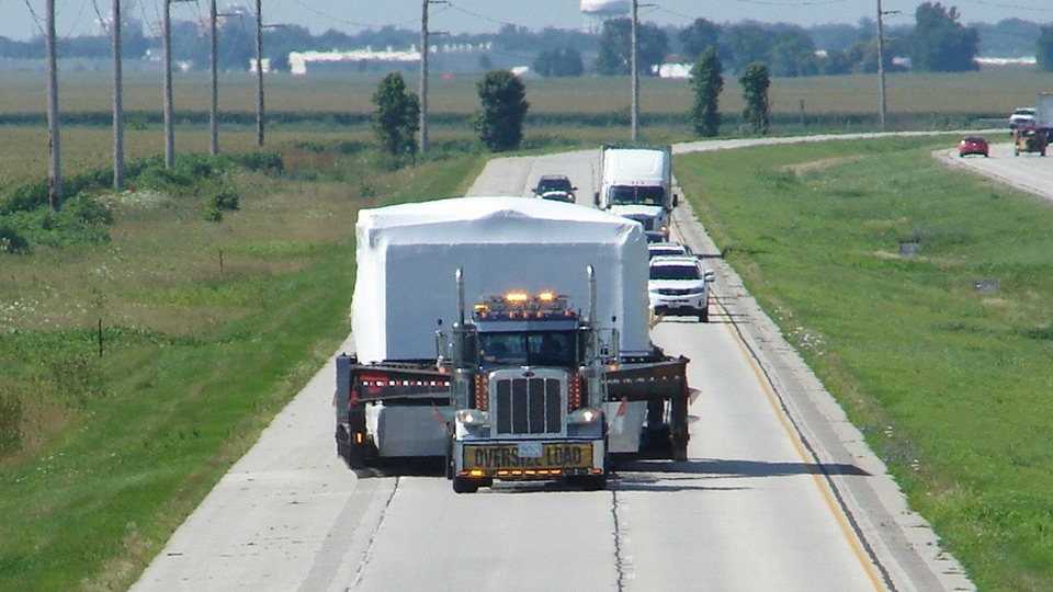 A front view of a oversize load taking up both lanes of the highway.
