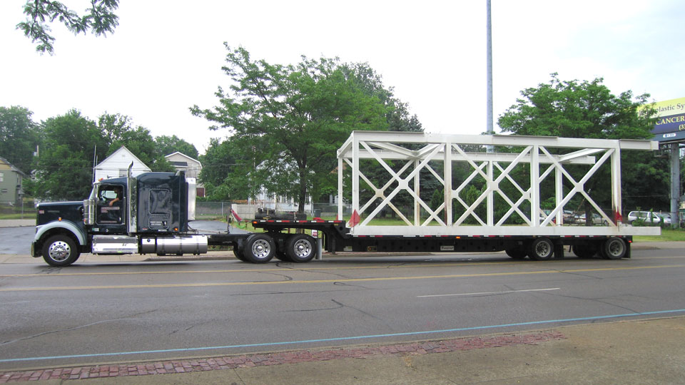 A standard stepdeck hauling a oversize load bridge section.