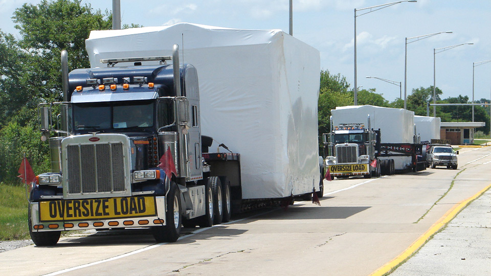 A group of 3 oversize loads parked along the side of a rest area in Illinois.