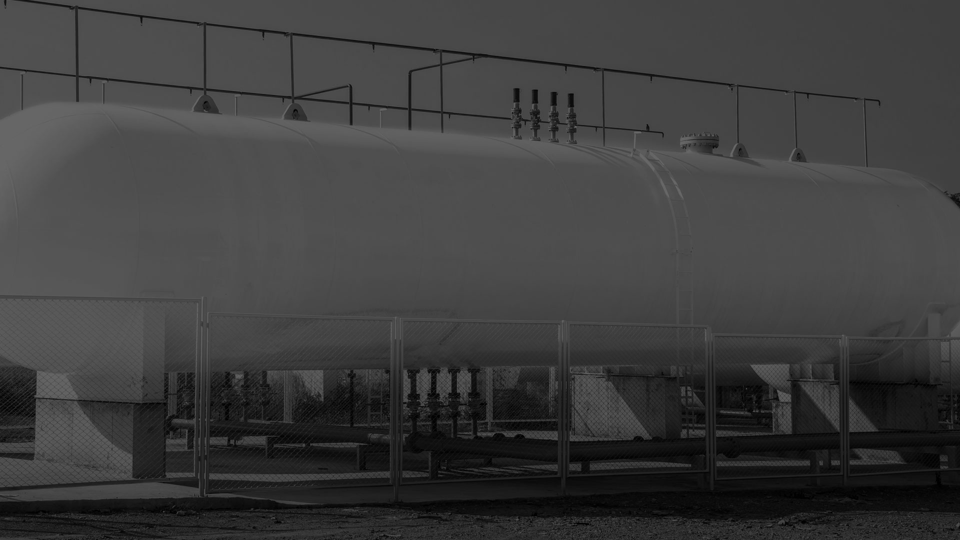 A darkened black and white image of a horizontal tank.