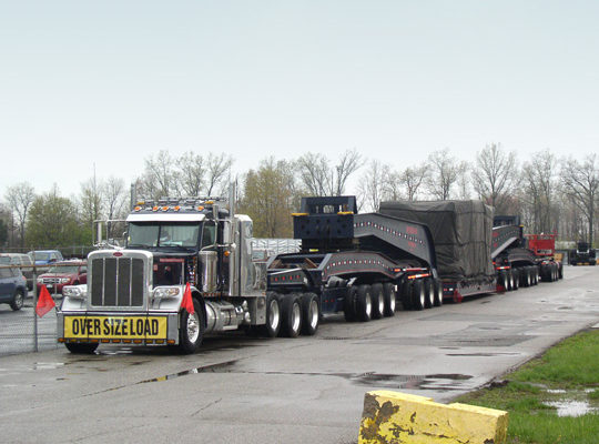 A 20 axle trailer, loaded with and injection mold machine clamp and sitting in a parking lot on an overcast day.