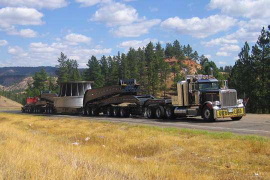 A large overside load moves uphill with blue cloudy skys, hills, and trees in the background.